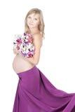 Ung härlig gravid kvinna med blommor arkivbild