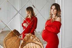 Ung härlig gravid kvinna med blont hår och försiktig makeup i den trendiga röda klänningen som poserar nära den stora spegeln på  royaltyfri bild