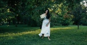 Ung härlig gravid kvinna med långt brunt hår i den vita klänningen 4K Den lyckliga kvinnan vänder omkring