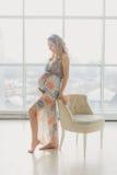 Ung härlig gravid kvinna som hemma står det near fönstret Arkivfoto