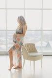 Ung härlig gravid kvinna som hemma står det near fönstret Arkivbilder