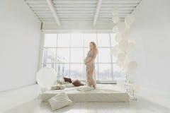 Ung härlig gravid kvinna som hemma står det near fönstret Arkivbild