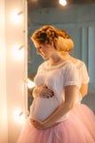 Ung härlig gravid kvinna som poserar i en tappninginre Arkivbilder