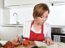 Ung härlig hem- kockkvinna i rött förkläde på kniv för innehav för recept för läs- kokbok för inhemskt kök följande royaltyfri bild