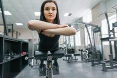 Ung härlig idrotts- kvinnabrunett som gör konditionövningar i idrottshallen Kondition sport, utbildning, folk, sund livsstil arkivfoto