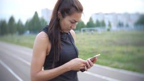 Ung härlig idrottskvinna på löparbana utomhus Färdig kvinna som använder mobiltelefonen arkivfilmer
