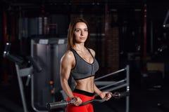 Ung härlig idrottskvinna som gör övningar i idrottshallen Royaltyfria Bilder