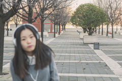 Ung härlig kinesisk flicka med hörlurar avsiktligt ut ur fokus Royaltyfri Bild