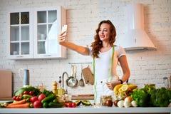 Ung härlig kvinna att ta en selfie, medan laga mat i det moderna köket Sunt mat- och bantabegrepp f?rlorande vikt royaltyfria bilder
