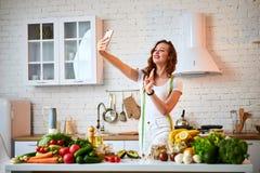 Ung härlig kvinna att ta en selfie, medan laga mat i det moderna köket Sunt mat- och bantabegrepp f?rlorande vikt arkivbilder