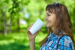 Ung härlig kvinna för stående som dricker kaffe i pappers- kopp royaltyfri fotografi