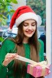 Ung härlig kvinna i ask för gåva för santas hattöppning Royaltyfri Bild