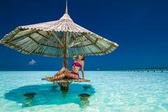 Ung härlig kvinna i bikinier under strandparaplyet i ocen royaltyfri fotografi