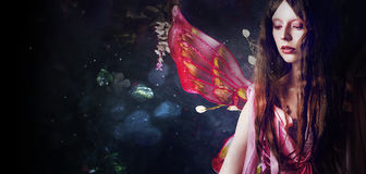 Ung härlig kvinna i bilden av feer, magisk mörk skog Royaltyfri Fotografi