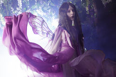 Ung härlig kvinna i bilden av feer, magisk mörk skog Arkivfoto