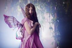 Ung härlig kvinna i bilden av feer, magisk mörk skog Royaltyfria Bilder