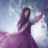 Ung härlig kvinna i bilden av feer, magisk mörk skog Arkivbild