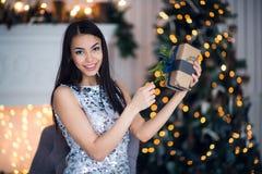 Ung härlig kvinna i den blåa eleganta aftonklänningen som sitter på golv nära julträd och gåvor på en helgdagsafton för nytt år arkivfoton