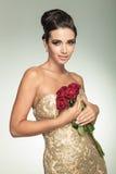 Ung härlig kvinna i den guld- klänningen som rymmer röda rosor royaltyfri foto