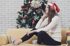Ung härlig kvinna i den röda hatten som sitter på soffan mellan christm royaltyfria foton