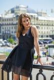 Ung härlig kvinna i den svarta klänningen som utomhus poserar i soligt oss Fotografering för Bildbyråer