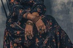 Ung härlig kvinna i elegant klänning med bohotillbehör som sitter på stol royaltyfri fotografi