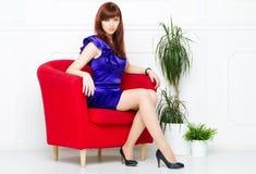Ung härlig kvinna i en röd stol royaltyfri bild