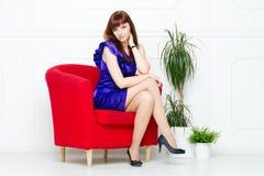 Ung härlig kvinna i en röd stol royaltyfri fotografi