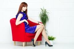 Ung härlig kvinna i en röd stol arkivbilder