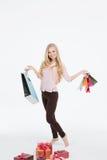 Ung härlig kvinna i ett hellångt med shoppingpåsar arkivfoton
