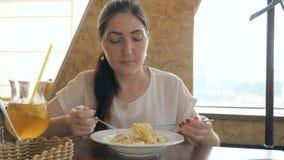 Ung härlig kvinna i ett kafé som äter en pasta stock video