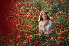 Ung härlig kvinna i ett vallmofält arkivfoto