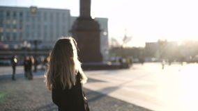 Ung härlig kvinna i grå färglag med långt hår som ler och poserar på kameramodemodell i centrum på solnedgången lager videofilmer