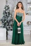 Ung härlig kvinna i grön elegant klänning i inre med ch royaltyfri fotografi