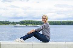 Ung härlig kvinna i jeans som sitter i sommargatamedeltal Fotografering för Bildbyråer