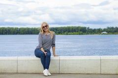 Ung härlig kvinna i jeans som sitter i sommargatamedeltal royaltyfri foto