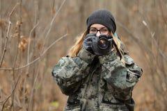 Ung härlig kvinna i kamouflagedräkten som upptäcker naturen i skogen med fotokameran Concep för loppfotografilivsstil Royaltyfria Foton