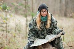 Ung härlig kvinna i kamouflagedräktsammanträde på skogjournalen som upptäcker naturen i skogen med kompasset och översikten Loppl Arkivfoto