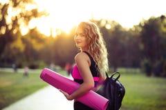 Ung härlig kvinna i sportswear Henne ` s som rymmer en utbildning matt Gå att göra sportar som utbildar, gymnastik utomhus royaltyfria bilder