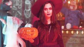 Ung härlig kvinna i svart häxadräkt på ett halloween parti arkivfilmer