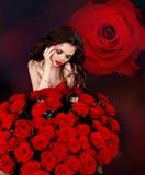 Ung härlig kvinna med buketten för röda rosor över blommor Arkivfoto