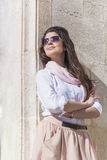 Ung härlig kvinna med den rosa halsduken mot stenväggen Royaltyfria Bilder