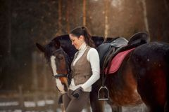 Ung härlig kvinna med den utomhus- ståenden för häst på vårdagen arkivfoto