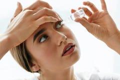 Ung härlig kvinna med Eyedrops Vision- och medicinbegrepp arkivfoton