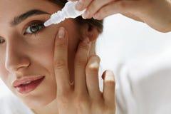 Ung härlig kvinna med Eyedrops Vision- och medicinbegrepp Arkivfoto
