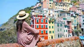Ung härlig kvinna med fantastisk sikt på den gamla byn Riomaggiore, Cinque Terre, Liguria, Italien Europeisk italienare lager videofilmer