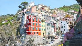 Ung härlig kvinna med fantastisk sikt på den gamla byn Riomaggiore, Cinque Terre, Liguria, Italien Europeisk italienare stock video