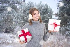 Ung härlig kvinna med gåvaaskar i vinterskog Fotografering för Bildbyråer