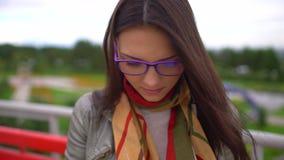 Ung härlig kvinna med glasögon som läser ett boksammanträde på en bänk utanför i en parkera i sommar Slutet av vänder mot upp 4 lager videofilmer