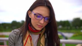 Ung härlig kvinna med glasögon som läser ett boksammanträde på en bänk utanför i en parkera i sommar Slutet av vänder mot upp 4 stock video